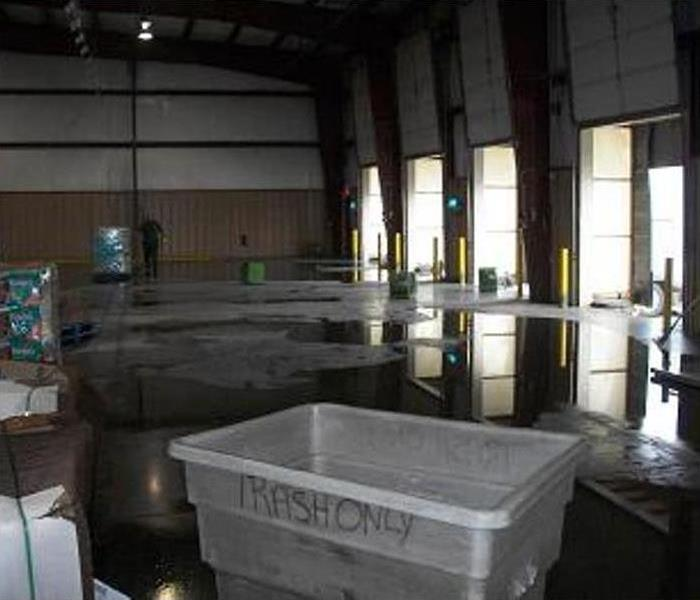 flooded concrete floor in open-bayed warehouse
