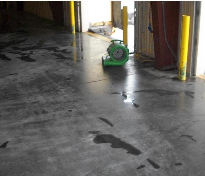 water removed from the warehouse floor, air mover completing the work