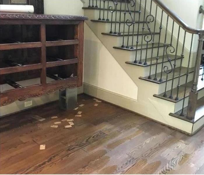 hardwood floorboards wet from flooding, furniture on blocks, stairway close by