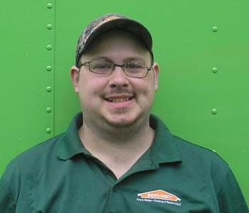 Male SERVPRO employee standing in front of a SERVPRO vehicle.